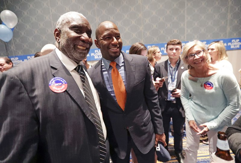 Former Florida Democratic gubernatorial nominee Andrew Gillum, center, greets supporters during a gathering at the Florida Democratic Party state conference, Friday, June 7, 2019, in Orlando, Fla. (AP Photo/John Raoux)