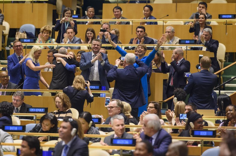 In this photo provided buy the United Nations, Estonian President Kersti Kaljulaid, center right in blue dress, raise her arms as she and her delegation rejoice after winning a seat on the United Nations Security Council, Friday, June 7, 2019, at United Nations headquarters. Estonia and the Caribbean island nation of St. Vincent and the Grenadines were elected to the U.N. Security Council on Friday, marking the first time the countries will hold seats on the U.N.'s most powerful body. (Loey Felipe/The United Nations via AP)