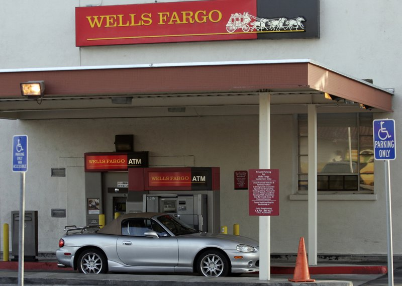 FILE - In this April 16, 2007, file photo, a customer banks from his vehicle at a Wells Fargo drive-thru ATM in the Atwater Village neighborhood of Los Angeles. Wells Fargo has agreed to pay at least $385 million to settle a California lawsuit alleging it signed up thousands of auto loan customers for costly car insurance without their consent, resulting in many having their vehicles repossessed. The bank filed the agreement Thursday, June 6, 2019, in a federal court in Santa Ana, Calif. It still needs a judge's approval. (AP Photo/Damian Dovarganes, File)