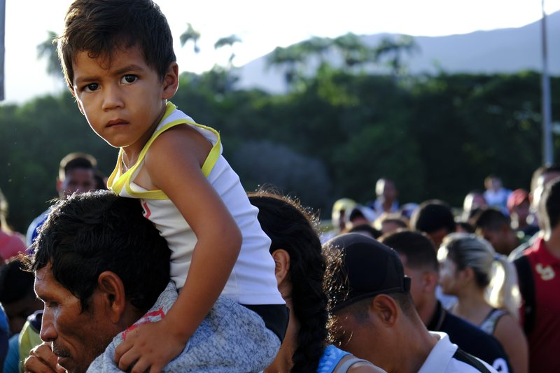 A Venezuelan man carrying a child on his shoulders lines up to cross the Simon Bolivar international bridge into Cucuta, Colombia, Saturday, June 8, 2019. Venezuela's President Nicolas Maduro ordered the partial re-opening of the border that has been closed since February when he stationed containers on the bridge to block an opposition plan to deliver humanitarian aid into the country. (AP Photo/Ferley Ospina)