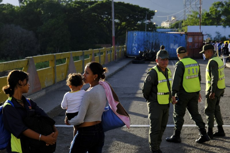 Venezuelans wait to cross the Simon Bolivar international bridge into Cucuta, Colombia, next to Bolivarian National Guard officers, Saturday, June 8, 2019. Venezuela's President Nicolas Maduro ordered the partial re-opening of the border that has been closed since February when he stationed containers on the bridge to block an opposition plan to deliver humanitarian aid into the country. (AP Photo/Ferley Ospina)