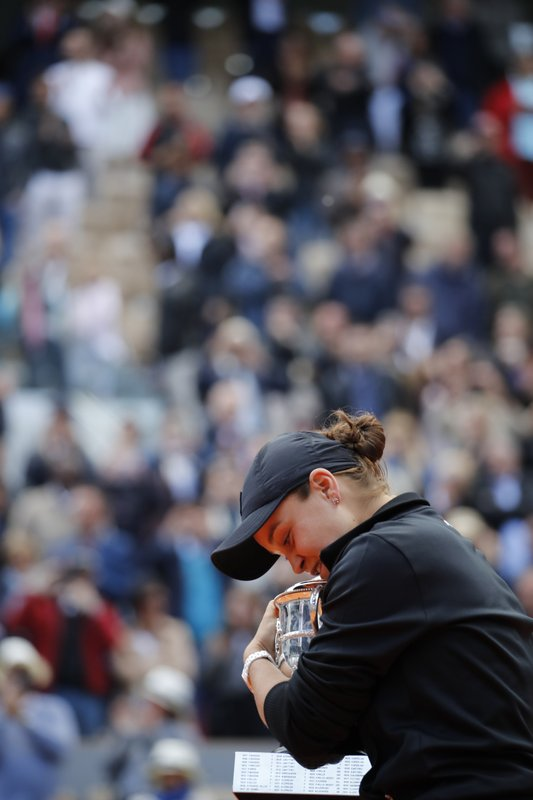 Australia's Ashleigh Barty hugs the trophy as she celebrates winning her women's final match of the French Open tennis tournament against Marketa Vondrousova of the Czech Republic in two sets 6-1, 6-3, at the Roland Garros stadium in Paris, Saturday, June 8, 2019. (AP Photo/Christophe Ena)