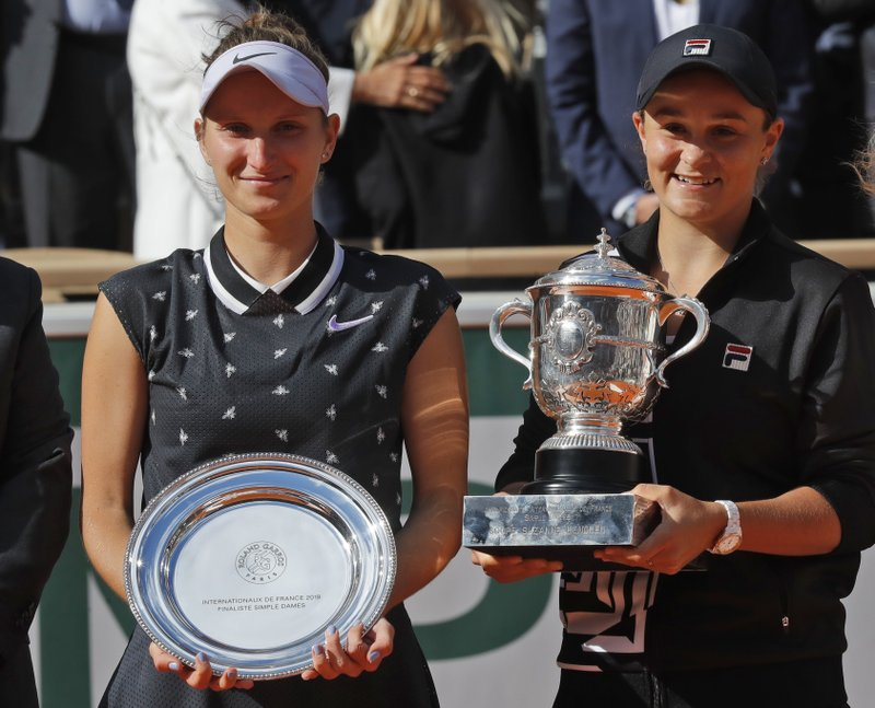 Australia's Ashleigh Barty, right, holds the trophy as she celebrates winning her women's final match of the French Open tennis tournament against Marketa Vondrousova of the Czech Republic, left, in two sets 6-1, 6-3, at the Roland Garros stadium in Paris, Saturday, June 8, 2019. (AP Photo/Michel Euler)