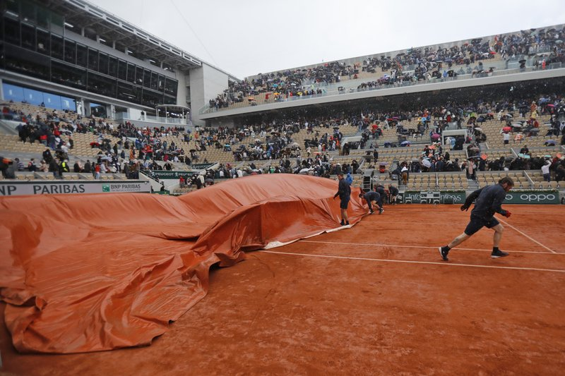 Workers run to cover center court as rain interrupted the men's semifinal match of the French Open tennis tournament between Serbia's Novak Djokovic and Austria's Dominic Thiem at the Roland Garros stadium in Paris, Saturday, June 8, 2019. (AP Photo/Michel Euler)