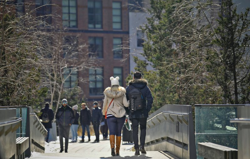 In this March 5, 2019 photo, visitors walking along the High Line in New York. An estimated 8 million visitors a year now visit the park, which threads 1.5 miles (2.4 kilometers) through an utterly transformed part of Manhattan now anchored at one end by the dazzling new home of the Whitney Museum of American Art and and at the other by Hudson Yards, a $25 billion development of skyscrapers, shops and a performing arts center. (AP Photo/Bebeto Matthews)