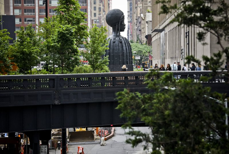 In this May 29, 2019 photo, visitors to the park gather near a bronze bust of a Black woman entitled