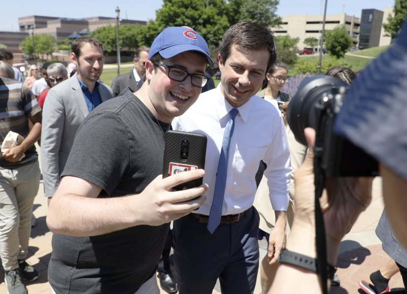 Democratic presidential candidate Pete Buttigieg, right, poses for a selfie during the Capital City Pride Fest, Saturday, June 8, 2019, in Des Moines, Iowa. (AP Photo/Charlie Neibergall)