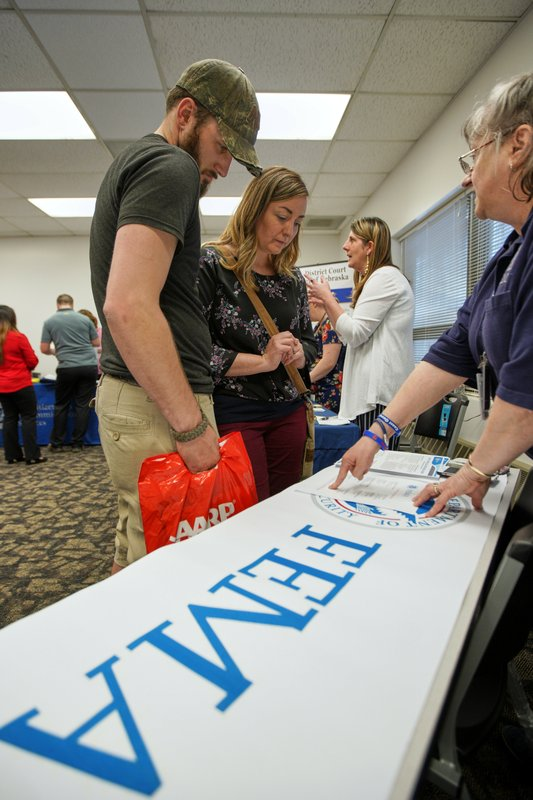 In this April 25, 2019 photo, April Kleinschmit and her husband Brandon , talk to FEMA representative Kristina Pooler, right, about available FEMA jobs, at a job fair in Lincoln, Neb. With federal disaster recovery staffers scrambling to meet needs amid floods, hurricanes and fires, they are now dealing with another issue _ historically low unemployment that's hampering their efforts to hire workers to help with the calamities. (AP Photo/Nati Harnik)