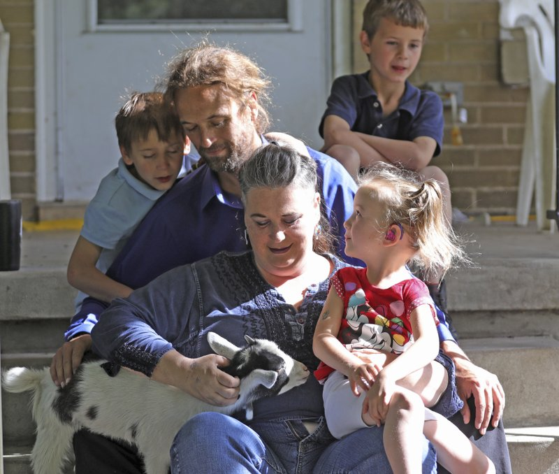 In this Thursday, June 6, 2019, photo, from left to right, Richard, dad Michael and mom Amie, Ethan, rear, and Victory, gather on the steps of their home, in Ogden, Utah. When doctors said her youngest child would be a girl, Amie Schofield chose the name Victoria. Then the prediction changed to boy, so she switched to Victor. It turned out neither was exactly right: The blue-eyed baby was intersex, with both male and female traits. She and her husband decided to call the infant Victory. The name is a hopeful promise for triumph over the secrecy and shame, the pain and discrimination suffered by intersex people. (AP Photo/Rick Bowmer)