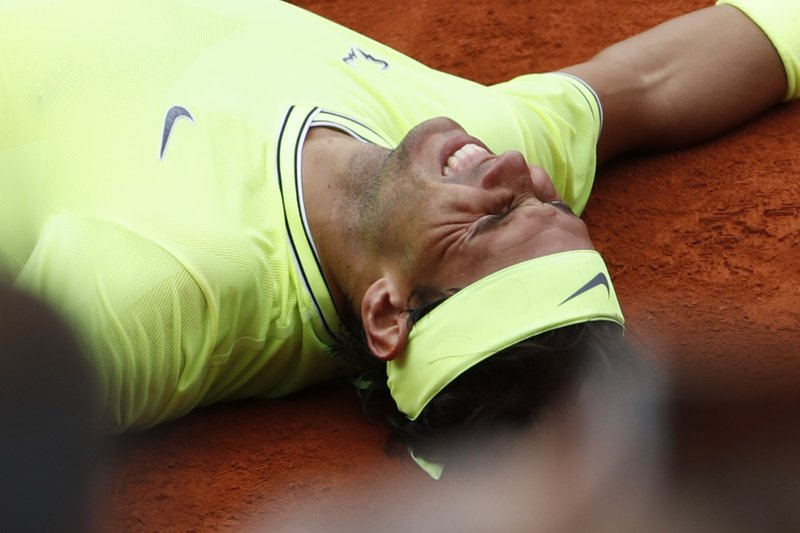 Spain's Rafael Nadal lays on the clay as he defeats Austria's Dominic Thiem during the men's final match of the French Open tennis tournament at the Roland Garros stadium in Paris, Sunday, June 9, 2019. Nadal won 6-3, 5-7, 6-1, 6-1. (AP Photo/Jean-Francois Badias)