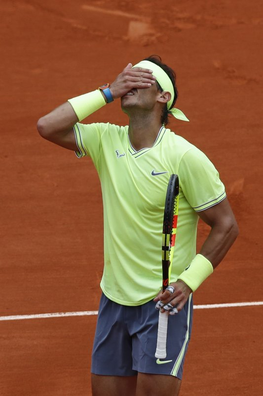Spain's Rafael Nadal covers his face after hitting a high ball into the net against Austria's Dominic Thiem during the men's final match of the French Open tennis tournament at the Roland Garros stadium in Paris, Sunday, June 9, 2019. (AP Photo/Christophe Ena)