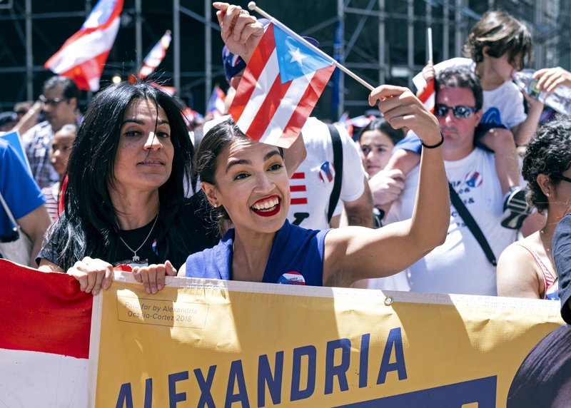 Rep. Alexandria Ocasio-Cortez, D-N.Y., center, takes part in the National Puerto Rican Day Parade Sunday, June 9, 2019, in New York. (AP Photo/Craig Ruttle))