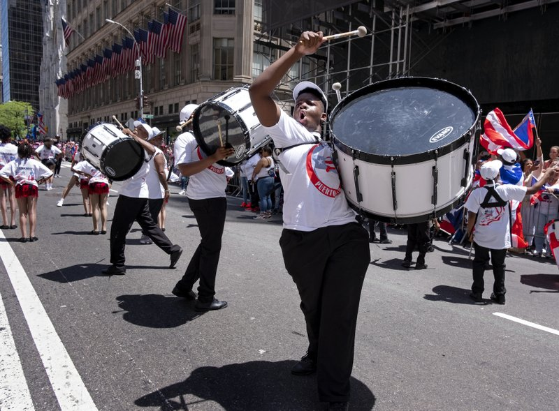 A parade unit entertains spectators during the National Puerto Rican Day Parade Sunday, June 9, 2019, in New York. (AP Photo/Craig Ruttle)