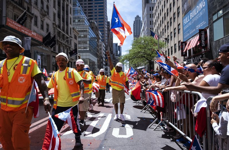 A parade unit walks along 5th Ave. during the National Puerto Rican Day Parade Sunday, June 9, 2019, in New York. (AP Photo/Craig Ruttle)
