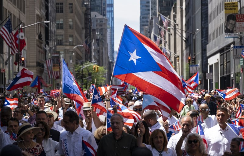 Hundreds of flags of Puerto Rico fly above people taking part in the National Puerto Rican Day Parade Sunday, June 9, 2019, in New York. (AP Photo/Craig Ruttle)