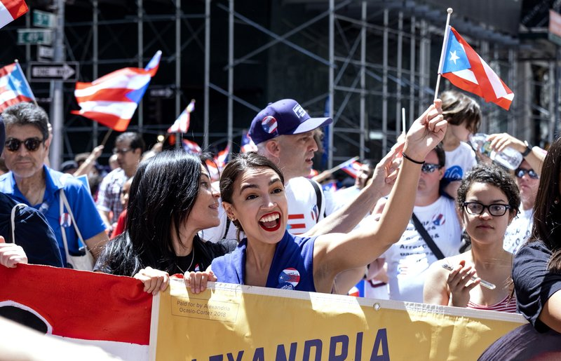 Rep. Alexandria Ocasio-Cortez, D-N.Y., center, takes part in the National Puerto Rican Day Parade Sunday, June 9, 2019, in New York. (AP Photo/Craig Ruttle)
