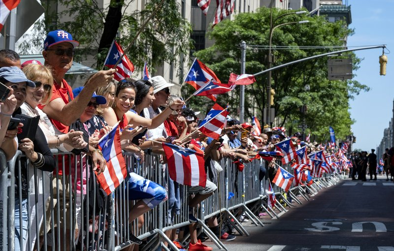 Spectators hold hundreds of flags of Puerto Rico as they watch the National Puerto Rican Day Parade Sunday, June 9, 2019, in New York. (AP Photo/Craig Ruttle)
