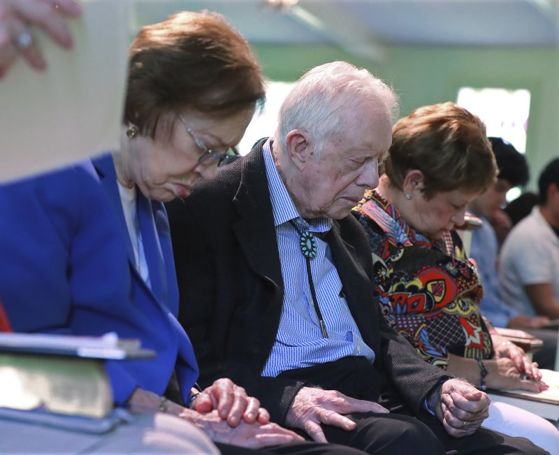 President Jimmy Carter and Rosalynn Carter bow their heads in prayer with members and visitors during the worship service at Maranatha Baptist Church less than a month after the 39th U.S. president and Plains native fell breaking his hip, on Sunday, June 9, 2019, in Plains, Ga.  (Curtis Compton/Atlanta Journal-Constitution via AP)