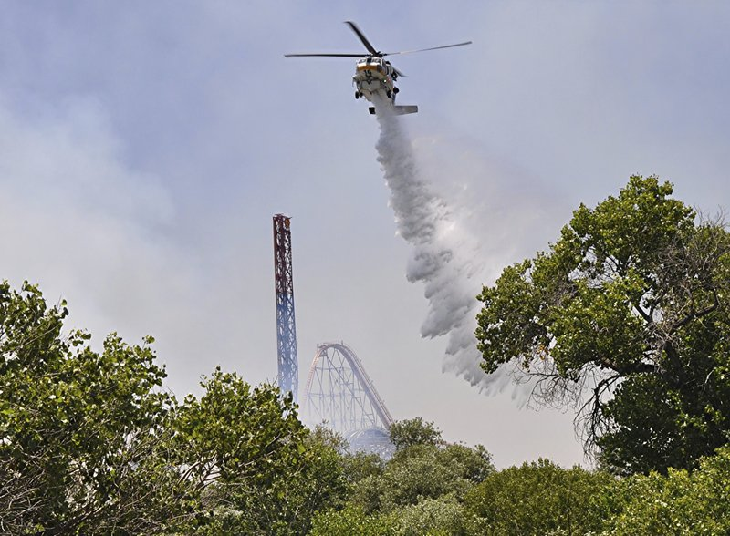 Los Angeles County Fire helicopter drops water on brush fire burning close to Six Flags Magic Mountain and Hurricane Harbor amusement park in Santa Clarita, Calif., Sunday, June 9, 2019. Heavy smoke surrounding Six Flags Magic Mountain and Hurricane Harbor prompted the park to announce an evacuation shortly after noon Sunday north of Los Angeles. But about 40 minutes later, the park said on its Twitter account that fire officials asked guests to stay at the park while they work to contain the blaze. Police closed access roads to the park off Interstate 5. (AP Photo/Rick McClure)