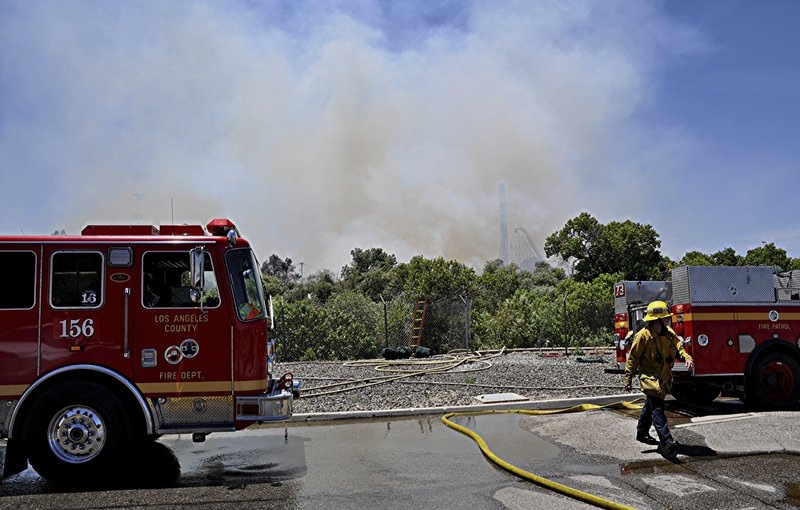 Los Angeles County firemen fight a brush fire burning close to Six Flags Magic Mountain and Hurricane Harbor amusement park in Santa Clarita, Calif., Sunday, June 9, 2019. Heavy smoke surrounding Six Flags Magic Mountain and Hurricane Harbor prompted the park to announce an evacuation shortly after noon Sunday north of Los Angeles. But about 40 minutes later, the park said on its Twitter account that fire officials asked guests to stay at the park while they work to contain the blaze. Police closed access roads to the park off Interstate 5. (AP Photo/Rick McClure)