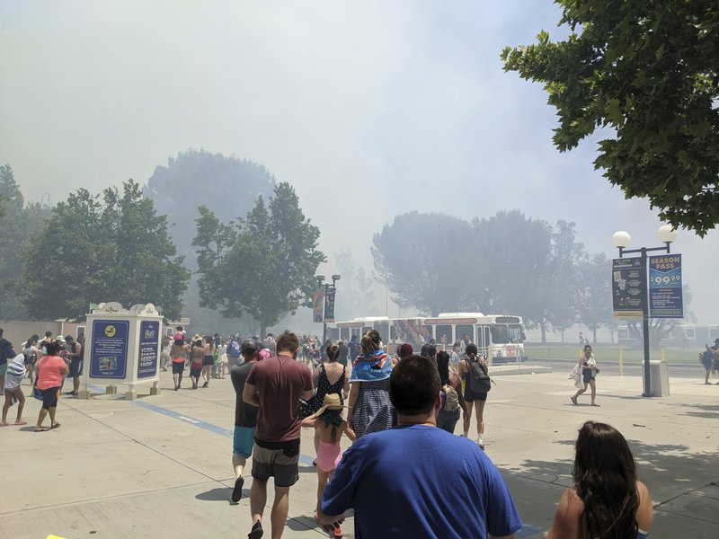 In this photo provided by Arthur Wilkie, people evacuate Six Flags Magic Mountain and Hurricane Harbor, Sunday, June 9, 2019, in Santa Clarita, Calif., north of Los Angeles, as smoke from a fast-moving brush fire surrounded the area. (Arthur Wilkie via AP)