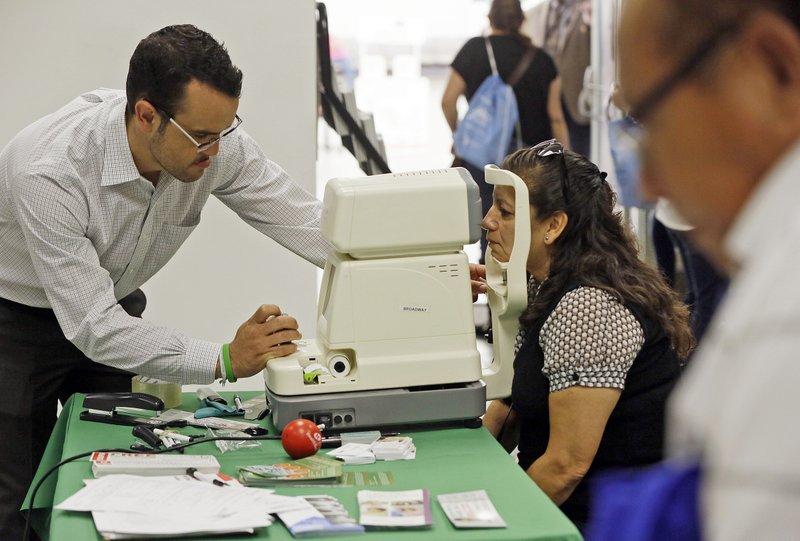 FILE - In this Oct. 1, 2013, file photo, Mexican national Rosa Guerra, right, gets a free eye exam during the Binational Health Week event held at the Mexican Consulate in Los Angeles. California will become the first state to pay for some adults living in the country illegally to have full health benefits as the solidly liberal bastion continues to distance itself from President Donald Trump's administration. (AP Photo/Damian Dovarganes, File)