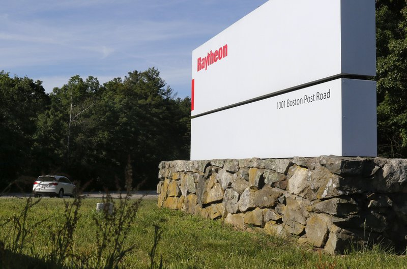 A car drives into the Raytheon facility Monday, June 10, 2019, in Marlborough, Mass. Raytheon Co. and United Technologies Corp. are merging in a deal that creates one of the world's largest defense companies. (AP Photo/Bill Sikes)