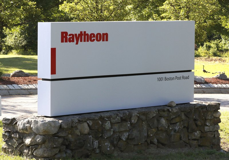 A sign stands at the road leading to the Raytheon facility Monday, June 10, 2019, in Marlborough, Mass. Raytheon Co. and United Technologies Corp. are merging in a deal that creates one of the world's largest defense companies. (AP Photo/Bill Sikes)