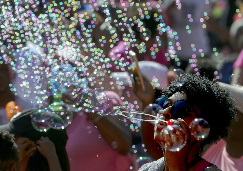 Trinity Newman blows bubbles along with thousands of people outside City Hall in honor of Maleah Davis, the four-year-old girl who went missing in early May and whose body was found tossed along an Arkansas roadside last week, on Sunday, June 9, 2019, in Houston. The city declared today