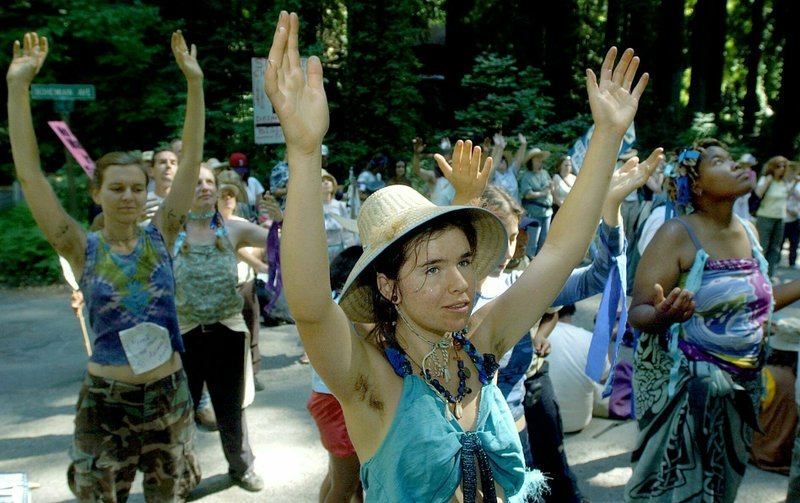 FILE - In this July 13, 2002, file photo, Tara Timberman, middle, of Occidental, Calif., demonstrates outside the gates of the Bohemian Grove, a private forested area near Monte Rio, Calif., during a protest against the Bohemian Club's annual meeting. A retreat for members of the elite Bohemian Club is facing renewed scrutiny for excluding women. This comes after the Sonoma County Board of Supervisors raised questions about whether sheriff's deputies should provide security for an event that discriminates by gender. (Kent Porter/The Press Democrat via AP, File)