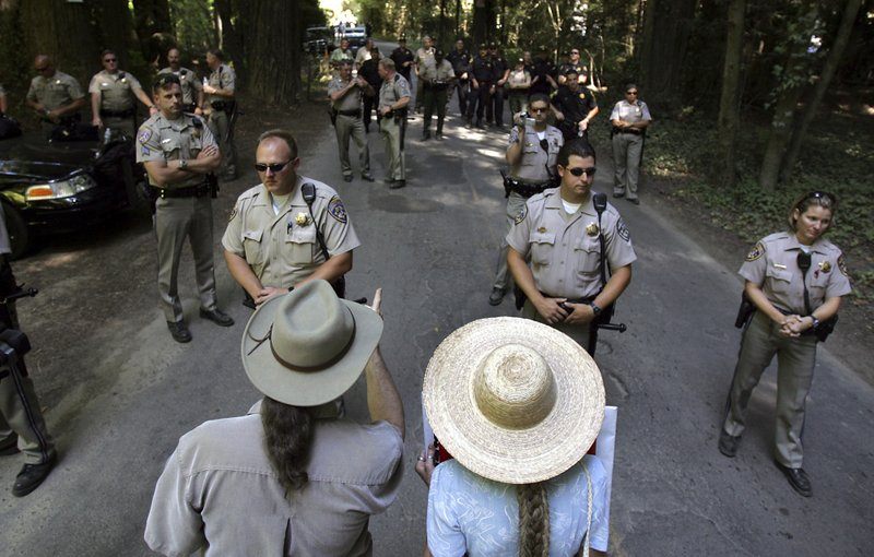 FILE - In this July 22, 2006 file photo, protesters Gary and Janet Evans of Sebastopol, Calif., try to talk with California Highway Patrol officers and Sonoma County Sheriff's deputies as they block off the entrance to the annual Bohemian Grove retreat, an exclusive California retreat for government and business leaders in Monte Rio, Calif. A retreat for members of the elite Bohemian Club is facing renewed scrutiny for excluding women. This comes after the Sonoma County Board of Supervisors raised questions about whether sheriff's deputies should provide security for an event that discriminates by gender. Female supervisors say they were inspired by the #MeToo movement and in threats to women's rights nationally. (Kent Porter/The Press Democrat via AP, File)
