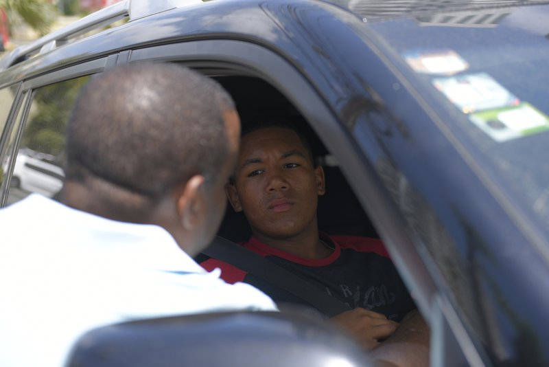 D'Angelo Ortiz, son of former Boston Red Sox slugger David Ortiz, sits in a vehicle outside the hospital where his father is being treated after he was shot the previous day in Santo Domingo, Dominican Republic, Monday, June 10, 2019. Doctors removed Ortiz's gallbladder and part of his intestine after the beloved former Boston Red Sox slugger known as Big Papi was ambushed by a gunman at a bar in his native Dominican Republic, a spokesman said Monday. (AP Photo/Roberto Guzmán)
