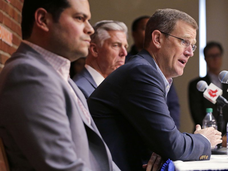 Boston Red Sox president Sam Kennedy, right, addresses the media during a news conference updating the status of former Red Sox designated hitter David Ortiz at Fenway Park in Boston, Monday, June 10, 2019. Ortiz was shot at a bar Sunday night in his native Dominican Republic. Team assistant general manager Eddie Romero, left, and president of baseball operations Dave Dombrowski, center rear, look on. (AP Photo/Charles Krupa)