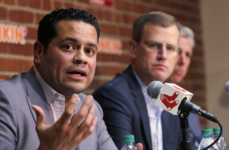 Boston Red Sox assistant general manager Eddie Romero, left, addresses the media during a news conference updating the status of former Red Sox designated hitter David Ortiz at Fenway Park in Boston, Monday, June 10, 2019. Ortiz was shot at a bar Sunday night in his native Dominican Republic. Team president Sam Kennedy looks on. (AP Photo/Charles Krupa)