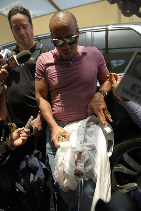 Eliezer Salvador, who said he took former Boston Red Sox slugger David Ortiz to the hospital after he was shot the day before, holds Ortiz's bloodied pants while speaking to the press outside the hospital where Ortiz is being treated in Santo Domingo, Dominican Republic, Monday, June 10, 2019. Doctors removed Ortiz's gallbladder and part of his intestine after the beloved former Boston Red Sox slugger known as Big Papi was ambushed by a gunman at a bar in his native Dominican Republic, a spokesman said Monday. (AP Photo/Roberto Guzmán)