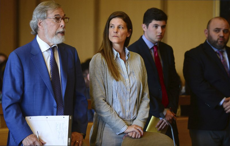 Michelle Troconis, center, listens as a member of her legal team Andrew Bowman, left, addresses the court during a hearing at Stamford Superior Court, Tuesday, June 11, 2019 in Stamford, Conn. Fotis Dulos, and his girlfriend, Michelle Troconis, have been charged with evidence tampering and hindering prosecution in the disappearance of his wife Jennifer Dulos. The mother of five has has been missing since May 24. (Erik Trautmann/Hearst Connecticut Media via AP, Pool)