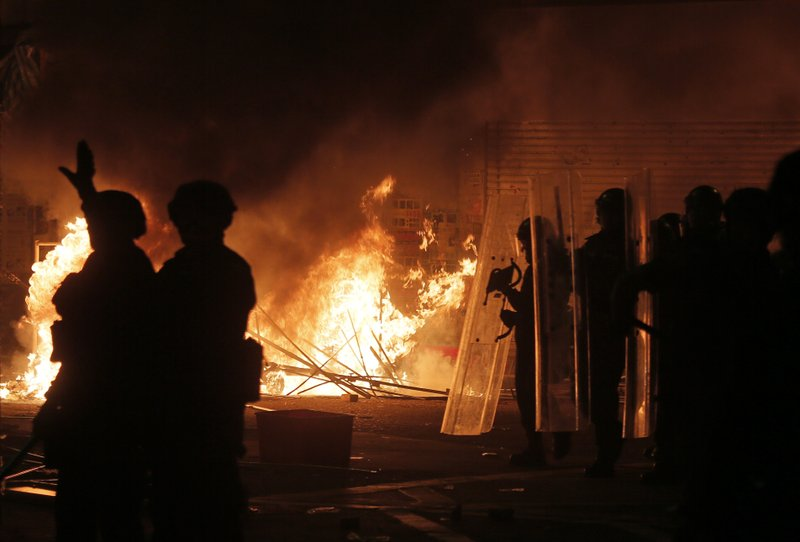 In this Tuesday, Feb. 9, 2016, file photo, police officers walk past fire set by protestors in Mong Kok district of Hong Kong, Hong Kong's Lunar New Year celebration descended into chaotic scenes as protesters and police clashed over a street market selling fish balls and other local holiday delicacies. (AP Photo/Vincent Yu)