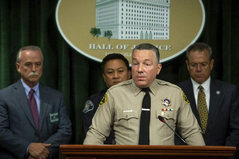 Los Angeles County Sheriff Alex Villanueva, with Sheriff's Homicide Capt. Kent Wegener, from left, Alhambra Police Chief Timothy Vu and LAPD Police Chief Michel Moore, announces during a news conference in Los Angeles on Tuesday, June 11, 2019. Rhett Nelson, 30, of St. George, Utah, was arrested Tuesday on suspicion of shooting an off-duty Los Angeles County sheriff's deputy at a fast-food restaurant Monday, and authorities say they are investigating whether he may have killed another man an hour earlier in attacks that both appear to be random. (Sarah Reingewirtz/The Orange County Register via AP)