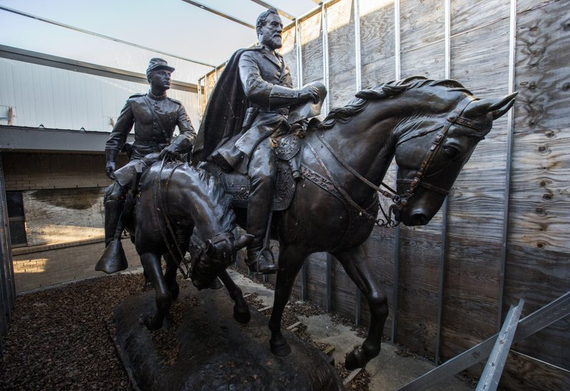 FILE--In this Dec. 20, 2018, file photo the 1935 statue of Robert E. Lee, right, and a young soldier by sculptor Alexander Phimister, sits in storage at Hensley Field, the former Naval Air Station on the west side of Mountain Creek Lake in Dallas. The buyer of the Lee statue for more than $1.4 million in a Dallas auction has been identified as a local law firm but the reason for the purchase still remains unclear. City leaders drew a top bid of $1,435,000 for the bronze sculpture from Dallas based Holmes Firm PC last week. The Dallas City Council is expected to vote on Wednesday, June 12, 2019 whether to approve the sale to the firm owned by Ronald L. Holmes. (Ashley Landis/The Dallas Morning News via AP, File)