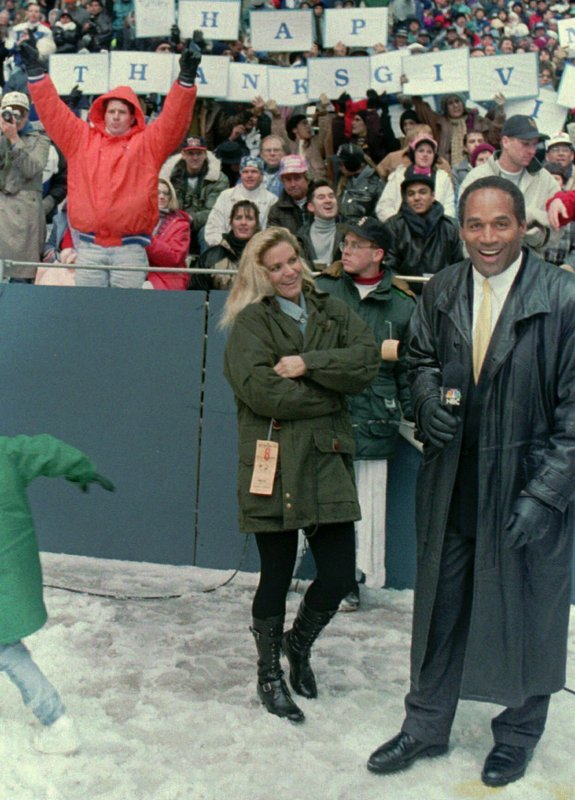FILE - In this Nov 25, 1993, file photo, O.J. Simpson stands with Nicole Brown Simpson while broadcasting on the sidelines during the Thanksgiving Day NFL football game in Irving, Texas. In a letter that surfaced after her 1994 murder, Nicole detailed the fear and violence that framed her marriage to charismatic football-star-turned-TV-pitchman O.J. Simpson. (AP Photo/Ron Heflin, File)