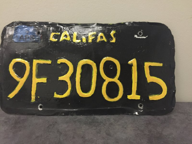 This undated photo provided by the Ventura County Sheriff's Department shows a phony license plate. A big-rig truck driver has been arrested after authorities spotted this phony license plate on his rig. Ventura County Sheriff's Department says the 1960s-style yellow-on-black plate had wobbly letters and numbers. Also, instead of