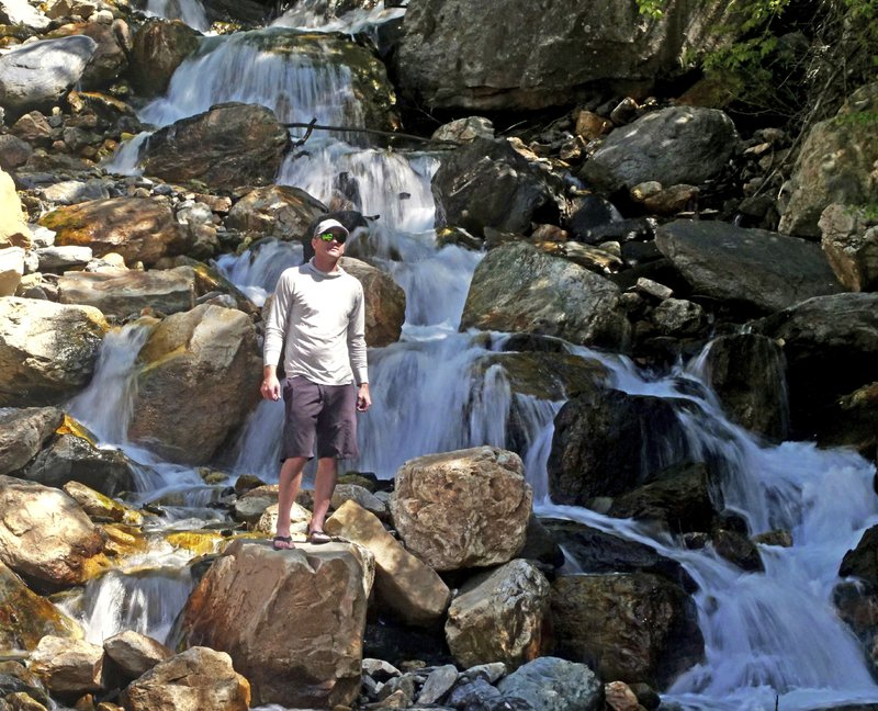 This Monday, June 10, 2019, photo shows hiker Tony Larsen posing for a photograph at a waterfalls, in the Big Cottonwood canyon, near Salt Lake City. The summer's melting snowpack is creating raging rivers that are running high, fast and icy cold. The state's snowpack this winter was about 150 percent higher than the historical average and double the previous year, which was the driest on record dating back to 1874, said Brian McInerney, hydrologist for the National Weather Service in Salt Lake City. (AP Photo/Rick Bowmer)