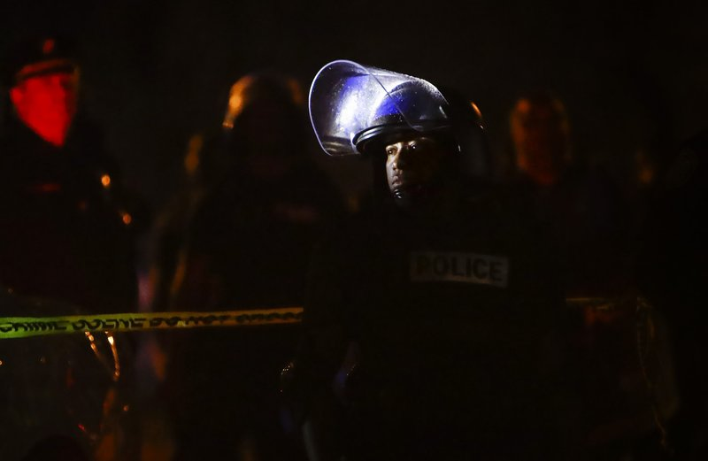 Memphis police maintain a perimeter around the crime scene after protesters took to the streets of the Frayser community in anger against the shooting of a youth by U.S. Marshals earlier in the evening, Wednesday, June 12, 2019, in Memphis, Tenn. Dozens of protesters clashed with law enforcement, throwing stones and tree limbs until authorities broke up the angry crowd with tear gas. (Mark Weber/Daily Memphian via AP)