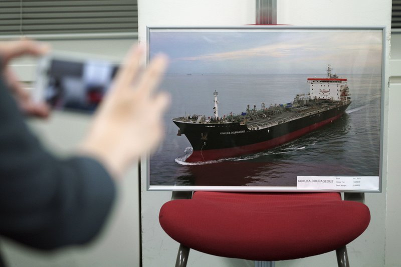 A journalist photographs a picture of the Kokuka Courageous, which was attacked near the Strait of Hormuz, at the Kikuka Sankyo Co., LTD office, owner of the Kokuka Courageous, Thursday, June 13, 2019, in Tokyo. (AP Photo/Eugene Hoshiko)