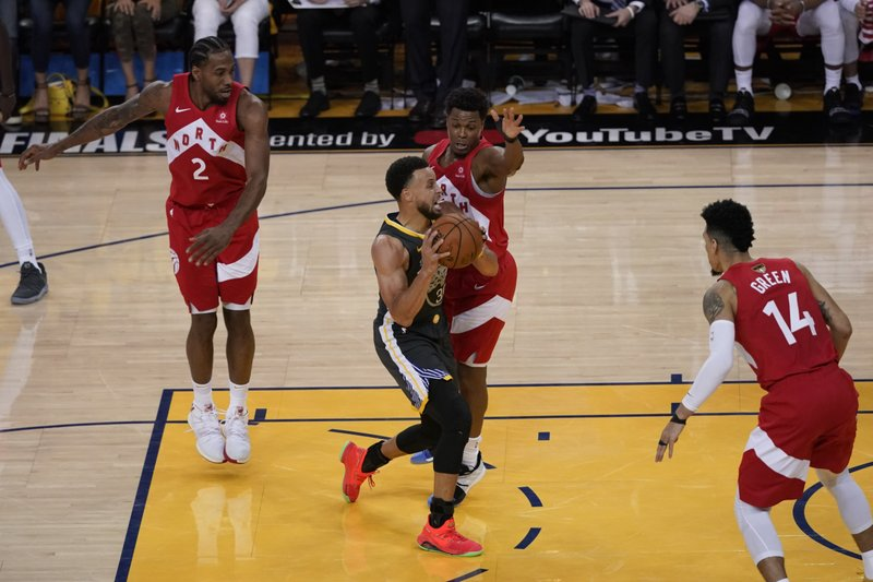 Golden State Warriors guard Stephen Curry, foreground, drives against Toronto Raptors guard Kyle Lowry during the first half of Game 6 of basketball's NBA Finals in Oakland, Calif., Thursday, June 13, 2019. (AP Photo/Tony Avelar)