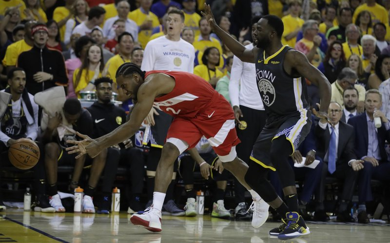 Toronto Raptors' Kawhi Leonard, left, chases a ball as Golden State Warriors' Draymond Green (23) defends during the second quarter of Game 6 of basketball's NBA Finals Thursday, June 13, 2019, in Oakland, Calif. (AP Photo/Ben Margot)