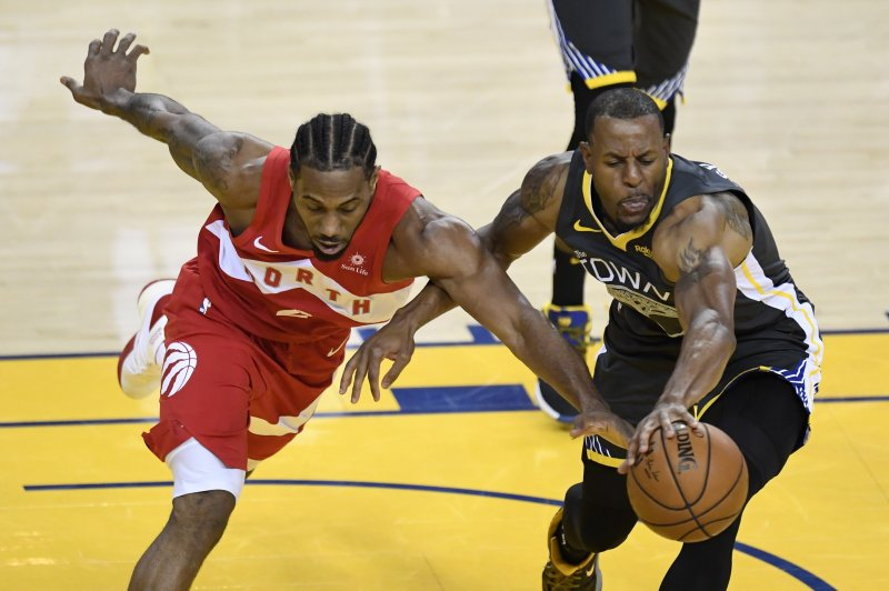 Toronto Raptors forward Kawhi Leonard, left, and Golden State Warriors forward Andre Iguodala reach for the ball during the first half of Game 6 of basketball's NBA Finals, Thursday, June 13, 2019, in Oakland, Calif. (Frank Gunn/The Canadian Press via AP)