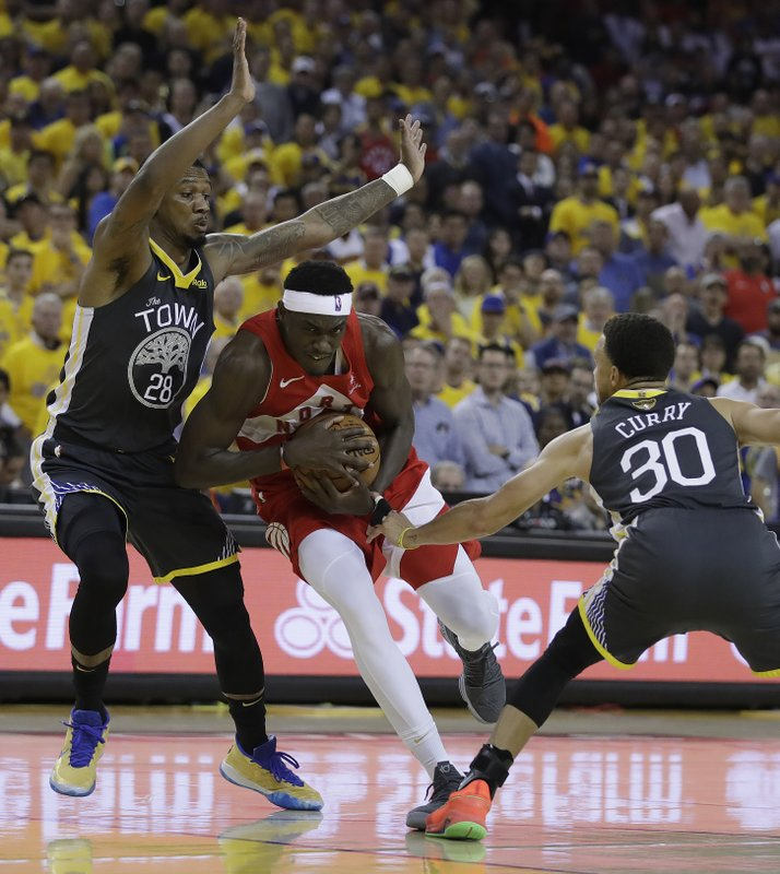 Toronto Raptors' Pascal Siakam, center, drives the ball between Golden State Warriors' Alfonzo McKinnie, left, and Stephen Curry (30) in the second quarter of Game 6 of basketball's NBA Finals Thursday, June 13, 2019, in Oakland, Calif. (AP Photo/Ben Margot)