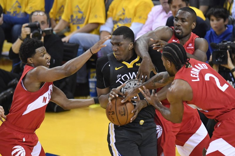 Golden State Warriors centre Kevon Looney is swarmed Toronto Raptors guard Kyle Lowry, left, center Serge Ibaka and forward Kawhi Leonard (2) during the first half of Game 6 of basketball's NBA Finals, Thursday, June 13, 2019, in Oakland, Calif. (Frank Gunn/The Canadian Press via AP)