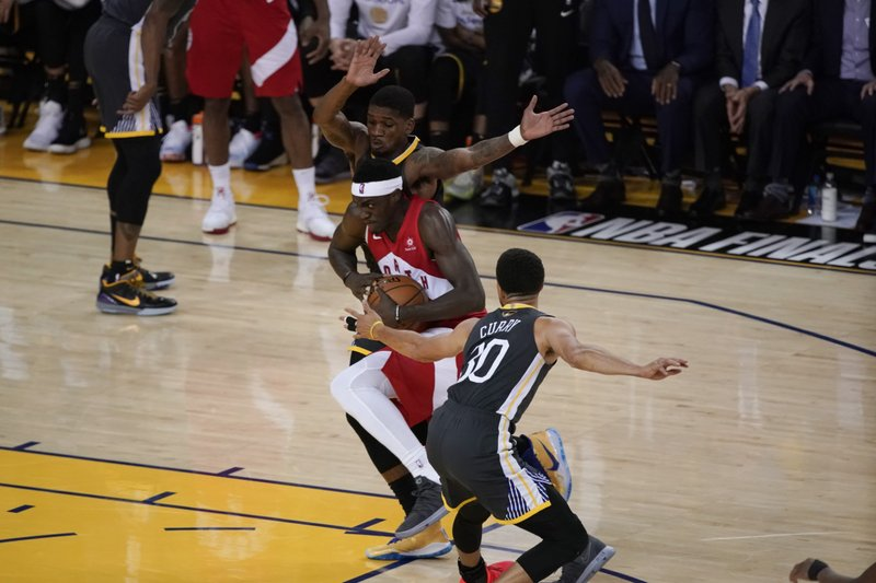 Toronto Raptors forward Pascal Siakam, middle, drives against Golden State Warriors forward Alfonzo McKinnie, top, and guard Stephen Curry (30) during the first half of Game 6 of basketball's NBA Finals in Oakland, Calif., Thursday, June 13, 2019. (AP Photo/Tony Avelar)